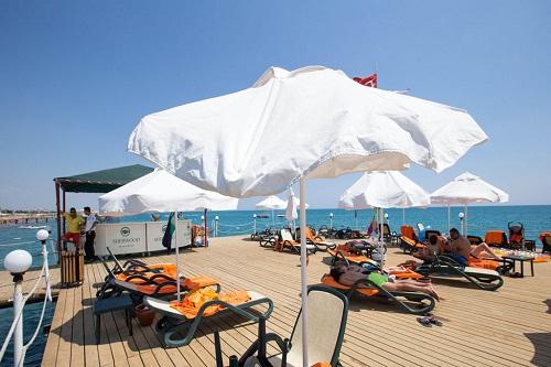 صندلی های مخصوص حمام آفتاب بر روی اسکلۀ ساحل اختصاصی هتل شروود لارا